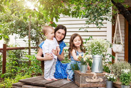 Young delighted mother sitting in armchair with adorable little siblings on terrace of country house and relaxing together during weekend