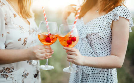 Anonymous female carrying goblet of alcohol cocktail with cherries and striped straw on blurred background of countryside