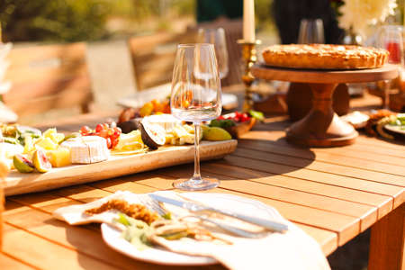 Empty wineglass placed near board with fruits on banquet table on sunny summer day 版權商用圖片