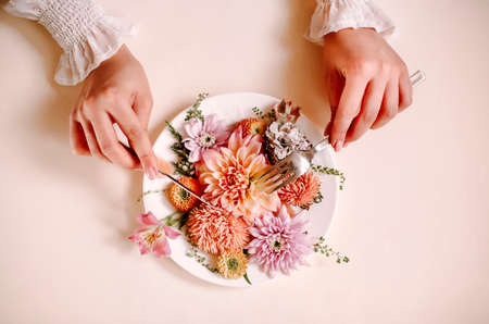 Top view of anonymous female with fork and knife cutting and eating natural flowers on plate against peach background