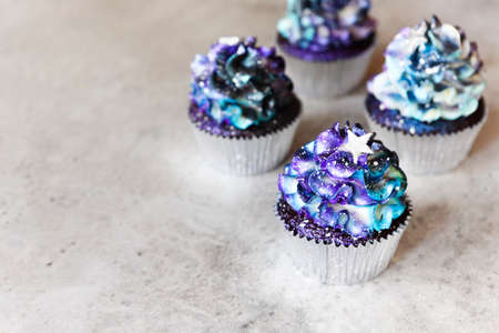 High angle of yummy cupcakes with galaxy colored cream and star shaped decoration placed on gray table