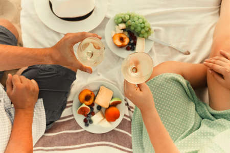 Top view of anonymous man and woman with wineglasses proposing toast over fruits during romantic picnic at the beach