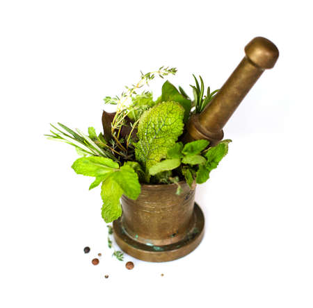 High angle of fresh herbs and pestle placed in bronze mortar isolated on white background