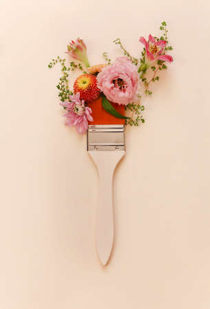 Top view of paintbrush placed near beautiful creative composition of natural flowers on beige background