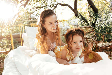 Young woman and cute little girl with fluffy rabbit relaxing on bed on sunny summer day in garden 版權商用圖片