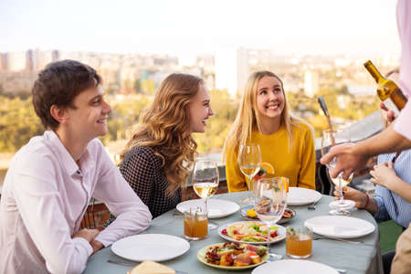 Cheerful man and women smiling while sitting at table during banquet 版權商用圖片