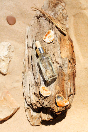 Top view of bottle with aromatic essential oil placed on rough wood near stones and twigs on sandy beach