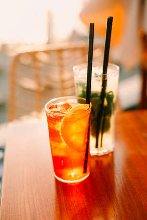 High angle of glasses with sweet cold cocktails and straws placed on table in bar on summer day