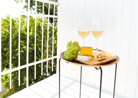Glasses of wine placed on table near cutting board with ripe grapes and cheese on sunny day on terrace