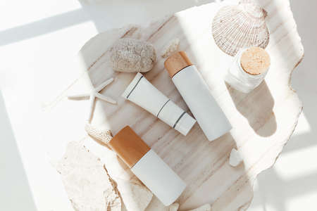 Top view of bottles of various cosmetic products placed amidst stones with seashell and starfish on white background