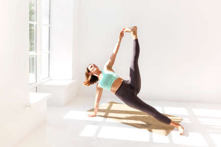 Side view of calm female in sportswear practicing yoga in Firefly pose while balancing on arms on mat and looking away