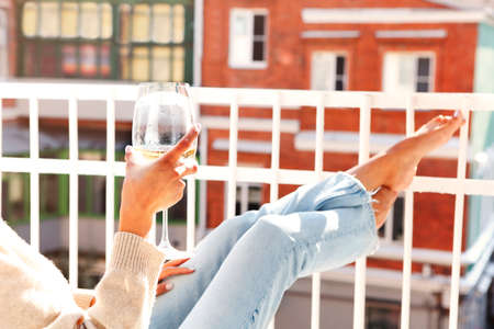 Crop barefoot female drinking wine and resting on balcony on sunny weekend day 版權商用圖片