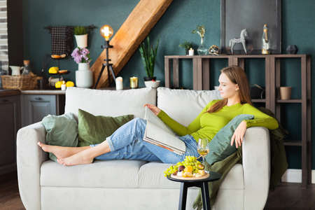 Side view of young female reading interesting magazine while lying on comfortable couch near table with fruits and wine on weekend day at home