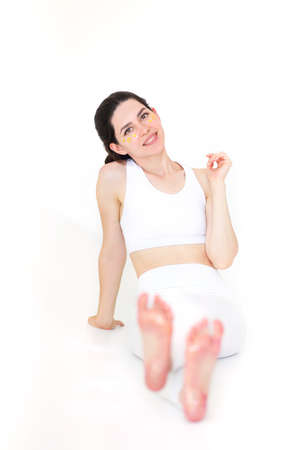 Bare feet of young female covered with shiny pink glitter on white background