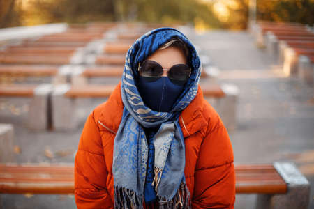 Blond female in stylish outerwear and fabric mask looking at camera while stitting on benche in park during pandemic