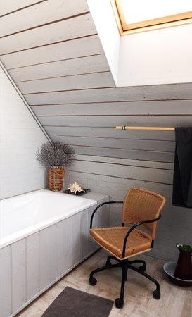 Comfortable chair placed near bathtub in stylish attic bathroom with gray wooden walls