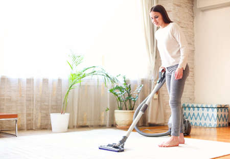 Full body young female using vacuum cleaner to tidy carpet in light room at home