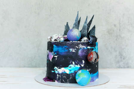 Yummy cake with galaxy colored cream and star shaped decoration placed on gray table 版權商用圖片