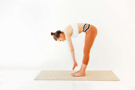 Young brunette female in sportswear on mat and doing yoga while practicing mindfulness. Physical and mental health concept 版權商用圖片