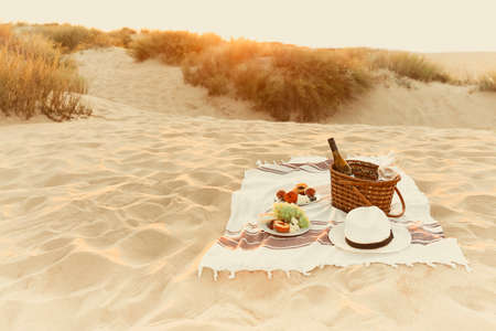 Basket with bottle of wine and plates with fresh fruits placed on blanket near hat during romantic picnic on sandy beach