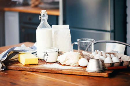 Assorted ingredients for pastry preparation placed on wooden chopping board on table in kitchen