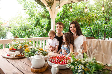 Loving family with kids sitting at table with delicious desserts and flowers during breakfast in countryside in summer