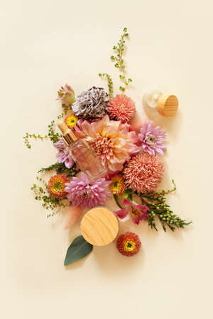 Top view of natural cosmetic products and fresh flowers arranged on beige background