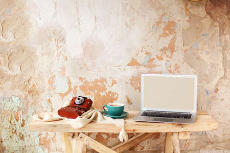 Retro photo camera and cup of fresh coffee placed on knitwear near modern netbook with blank screen on wooden table against grungy plaster wall in creative studio 版權商用圖片