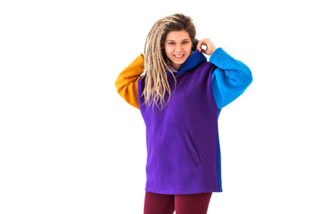 Cheerful young female in colorful outfit looking at camera with smile and shaking dreadlocks isolated on white background