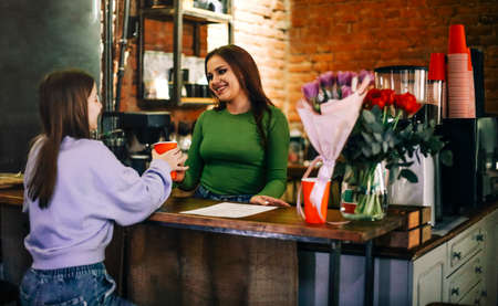 Cheerful young woman giving cup of fresh beverage to female customer while working in cafe 版權商用圖片