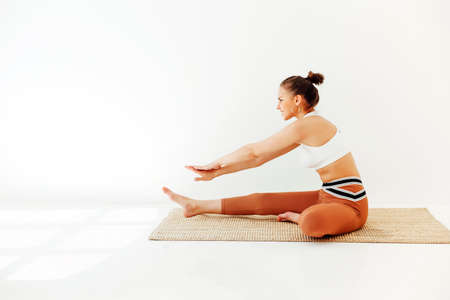 Young brunette female in sportswear sitting on mat and doing yoga while practicing mindfulness. Physical and mental health concept