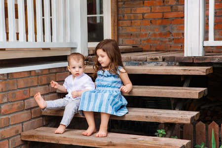 Cute little brother and sister sitting on wooden staircase near porch of country house and relaxing in rural area during summer holiday 版權商用圖片