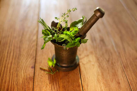 High angle of fresh herbs and pestle placed in bronze mortar isolated on the table 版權商用圖片