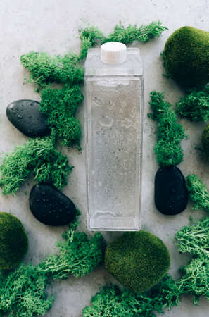 Top view of transparent container of fresh water surrounded with moss and pebbles on gray stone surface