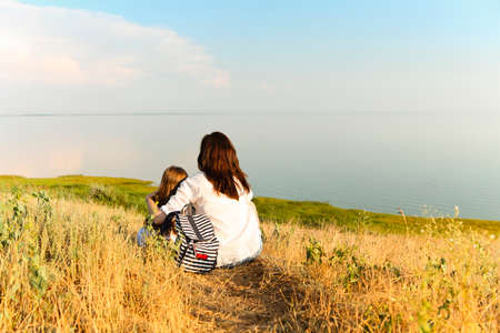 Back view of unrecognizable woman hugging girl while sitting on dried grass and admiring picturesque seascape during summer weekend 版權商用圖片