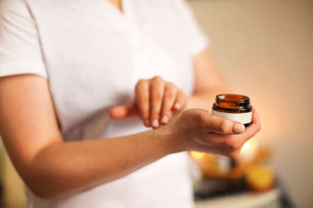 Unrecognizable crop female beautician applying cream from jar on hand before procedure in salon