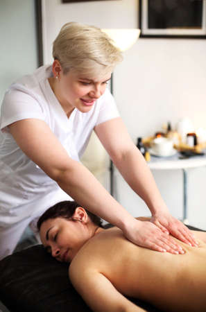 Faceless master giving massage of back and shoulder muscles to anonymous woman lying on table in spa salon