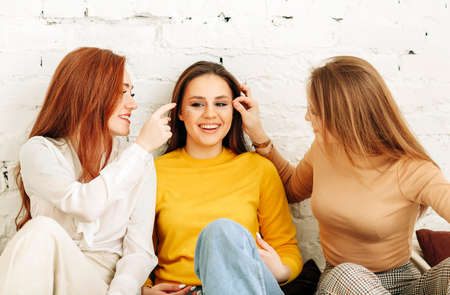 Optimistic young women smiling and touching face of stylish girlfriend while resting near rough brick wall Reklamní fotografie