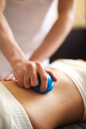 Faceless masseur rubbing back of customer with help of rubber vacuum cup working in salon