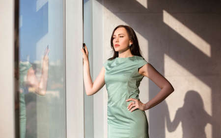 Low angle of stylish female entrepreneur looking away in sunlit workspace
