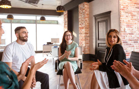 Woman in smart casual clothes sitting on chair and talking with workers during meeting in modern workplace