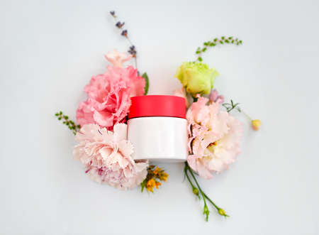 Top view of jar of face cream made from natural plant ingredients, oils and herbs, carnation and rose flowers on white blank background, vertical shot. Organic cosmetics concept