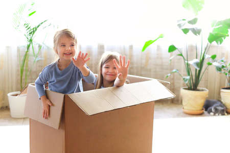Big carton box with cheerful girls waving hands while playing at home in weekend together