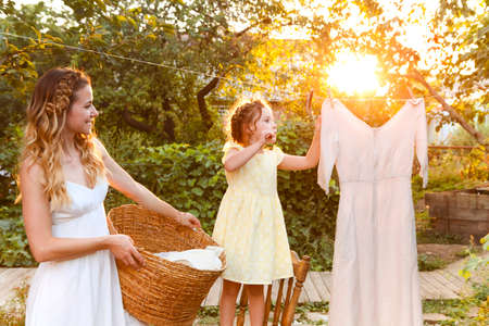 Charming little girl helping mother with wicker basket while doing chore and hanging laundry in backyard in summer evening