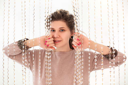 Smiling beautiful brunette woman with piercing in nose looking at camera pushing interior curtains of glass transparent beads with her hands, standing isolated over bright white background