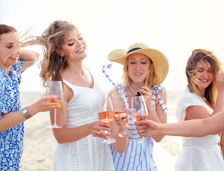 Happy female friends in summer dresses smiling and clinking glasses of wine while resting on beach together