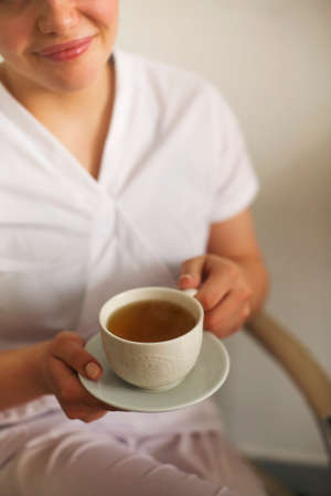 Cropped photo of happy lovely young female health worker laughing sincerely while holding cup of hot tea, enjoying coffee break and spending time with coworkers in medical clinic. Vertical shot