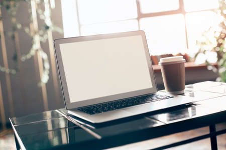 Photo of white blank screen of laptop with keyboard case lying on little table with disposable cup of coffee from cafeteria next to computer over comfortable living room interior background Фото со стока