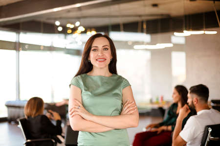 Woman in smart casual clothes sitting on chair with workers during meeting in modern workplace Фото со стока