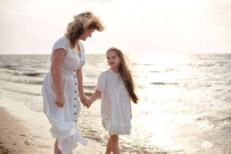 Full body cheerful woman in white dress embracing girl while standing on beach near waving sea in morning Фото со стока